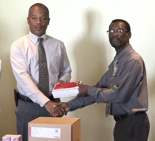 Senior Pastor and Island Coordinator of the Seventh Day Adventist Church Stanton Adams presents lab equipment to Hospital Administrator Gary Pemberton at a ceremony at the Alexandra Hospital on March 15, 2017