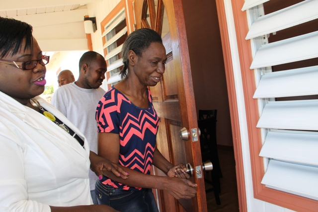 Ms. Lynette Koram of Jessups Village opens the door to her new home with her son Lesroy, at Jessups Village moments after receiving the keys from Junior Minister in the Ministry of Social Development Hon. Hazel Brandy-Williams on March 10, 2017