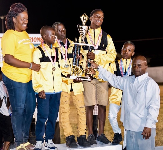 Athletes of the Elizabeth Pemberton Primary School, winners of the B Division in the 25th Gulf Insurance Primary School Championships receive trophy from Permanent Secretary in the Premier's Ministry Wakely Daniel at the trophy ceremony at the Elquemedo T. Willett Park on April 05, 2017. Head teacher Shenelle Pemberton looks on (photo courtesy Corner Stone)