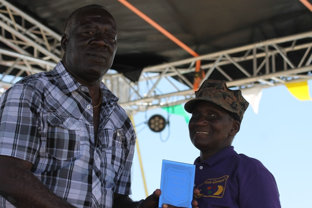 Augustine Merchant, IICA Coordinator for the Delegation in St. Kitts and Nevis presents a plaque to Mrs. Emmontine Thompson for her Outstanding Performance and Contribution to the Crops Sector in 2016 at the 23rd Annual Agriculture Open Day at the Villa Grounds on Nevis on March 30, 2017