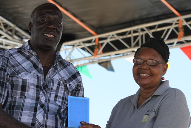 Augustine Merchant, IICA Coordinator for the Delegation in St. Kitts and Nevis presents a plaque to Mrs. Maureen Stapleton for her Outstanding Performance and Contribution to the Agro-Processing Sector for 2016 at the 23rd Annual Agriculture Open Day at the Villa Grounds on Nevis on March 30, 2017