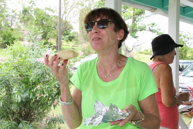 Mary Kay, from the United States of America sampling a traditional coconut tart at the Ministry of Tourism's Open Day on May 11, 2017, at the Nevisian Heritage Village in Fothergills