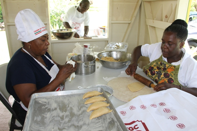 Patricia Thompson, Manager of the Nevisian Heritage Village (l) and Lydia Lawrence making coconut tarts while Mr. Winston Fyfield prepares rolls for baking at the Ministry of Tourism's Exposition Nevis Open Day at the Heritage Village at Fothergills on May 11, 2017