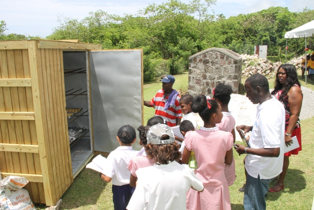 "Students of the Montessori Academy Nevis with Principal Denis Morgan, tour guide John Hanley, Acting Permanent Secretary in the Ministry of Tourism and the baker Oliver ""Powers"" Liburd experiencing what life was like in Nevis at the Nevisian Heritage Village during the Ministry of Tourism's Open Day, a part of Exposition Nevis on May 11, 2017"