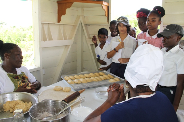 Patricia Thompson, Manager of the Nevisian Heritage Village accompanied by Lydia Lawrence of the Ministry of Tourism, tells students of the Montessori Academy Nevis about making tarts the Nevis way at the Nevisian Heritage Village during the Ministry of Tourism's Open Day, a part of Exposition Nevis on May 11, 2017