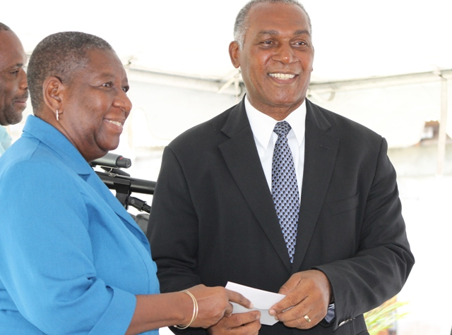 Dr. Robertine Chaderton, Chairperson of the Sugar Industry Diversification Fund Board of Counsellors hands over the third instalment of a $9million commitment to Premier of Nevis and Minister of Finance Hon. Vance Amory at the ground breaking ceremony on May 31, 2017, for construction of the $18million Alexandra Hospital Expansion Project