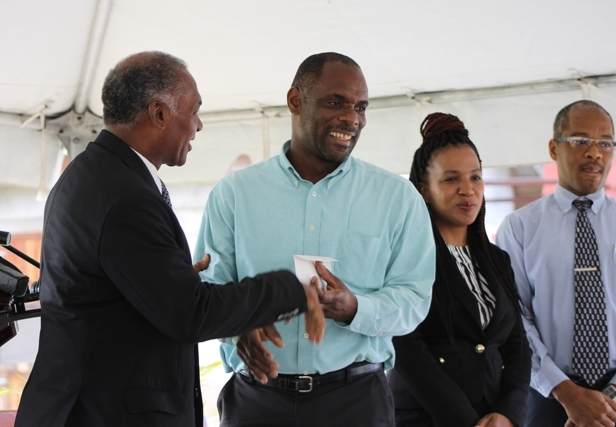 (l-r) Premier of Nevis and Minister of Finance Hon. Vance Amory hands over cheque from the Sugar Industry Diversification Fund to Permanent Secretary in the Ministry of Finance Colin Dore at the ground breaking ceremony on May 31, 2017, for construction of the $18million Alexandra Hospital Expansion Project. Permanent Secretary in the Ministry of Health Nicole Slack-Liburd and Hospital Administrator Gary Pemberton look on