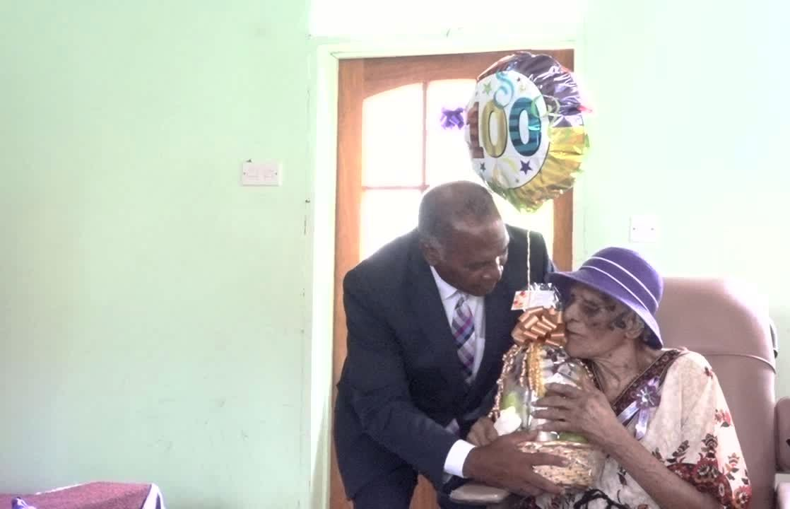 Premier of Nevis Hon. Vance Amory presents Eileen Swanston Smithen with a birthday gift at a thanksgiving service in celebration of her 100th birthday on June 20, 2017, at the Zion Gospel Hall