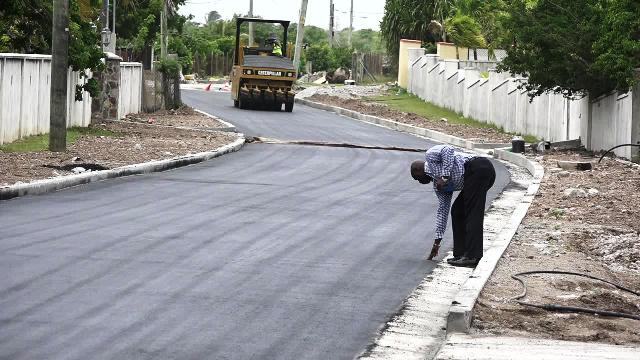 A section of the 2,400 feet of Shaws Road being asphalted by the workmen from the Public Works Department on Nevis on June 14, 2017, while Hon. Alexis Jeffers, Minister of Communication and Works on Nevis Minister checks the surface