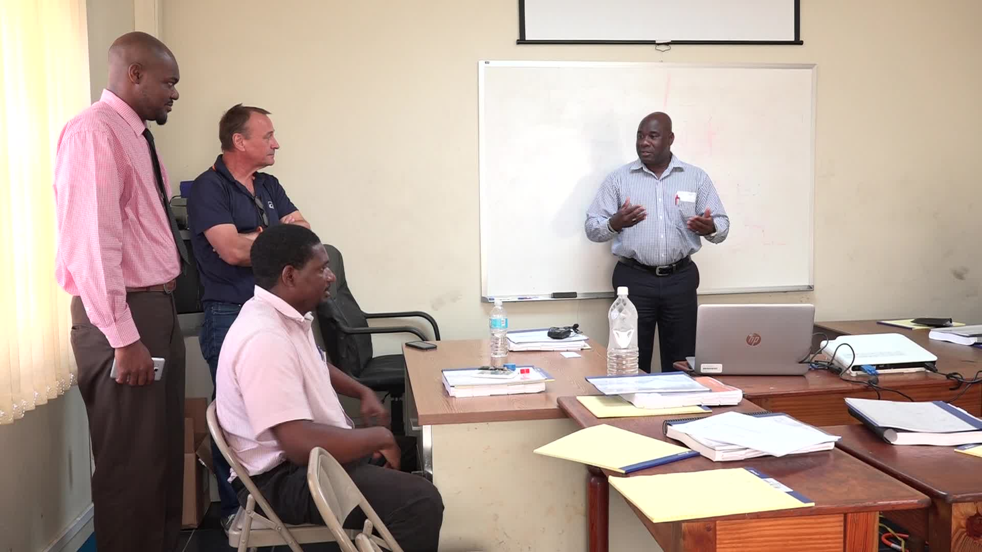 (l-r standing) Mr. Michael Webbe, Nevis Electricity Company Limited's Senior Human Resource Officer, Mr. Matti Kakko, Senior Instructor Technical Service Turbochargers Wӓrtsilӓ North America Inc. and a participant at the Nevis Electricity Company Limited training session July 31, 2017 at the Prospect Power Plant meeting room listening to Hon. Alexis Jeffers, Minister of Public Utilities on Nevis