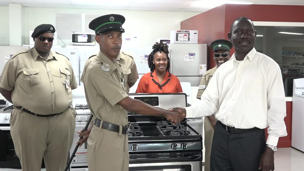 Acting Permanent Secretary in the Ministry of Tourism Mr. John Hanley hands over a new stove to Mr. Desmond Morton, Principal Officer at the Prison Farm on Nevis at the Horsfords Nevis Furniture and Appliances store on July 26, 2017. Looking on are (back left to right) Prison Officers Mc Mully Isaac and Jermaine Hendrickson, Ms. Sylvia Dore, Administrative Assistant in the Ministry of Tourism and Prison officer Sergeant Stanford Browne