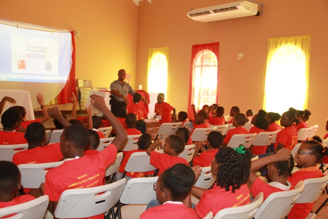 An officer of the Royal St. Christopher and Nevis Police Force in a session on Crime and Violence with primary school students at the St. Kitts and Nevis Fire and Rescue Service, Nevis Division 15th Annual Summer Safety Programme at the Jessups Community Centre on July 03, 2017