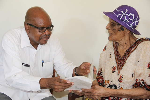 Governor General of St. Kitts and Nevis His Excellency Sir Tapley Seaton presents a royal birthday card from Her Majesty Queen Elizabeth II to centenarian Eileen Swanston Smithen at her home in Zion Village, Gingerland on July 13, 2017, after some mailing delay