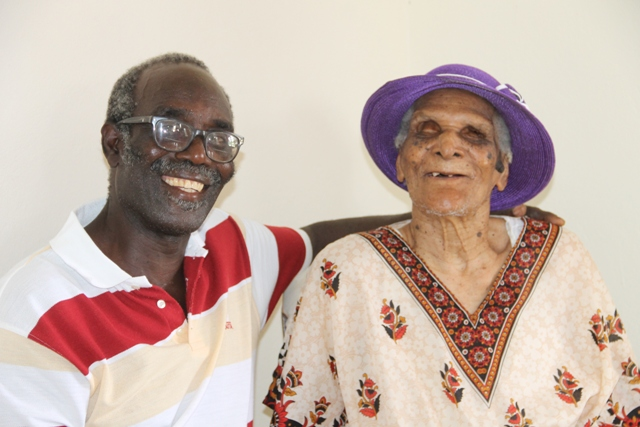 Centenarian Eileen Swanston Smithen with her adopted son and caretaker Pastor Theophilus Kelly, moments after she received a royal birthday card from Her Majesty Queen Elizabeth II on the occasion of her 100th birthday from Governor General of St. Kitts and Nevis His Excellency Sir Tapley Seaton at her home in Zion Village on July 13, 2017