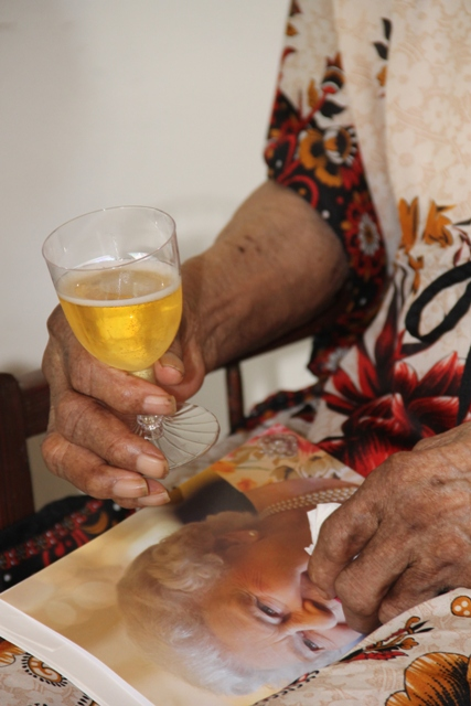 Centenarian Eileen Swanston Smithen holds her royal birthday card from Her Majesty Queen Elizabeth II in one hand and a glass of chilled cider in the other, after receiving the card from Governor General of St. Kitts and Nevis His Excellency Sir Tapley Seaton at her home in Zion Village on July 13, 2017, to mark her 100th birthday