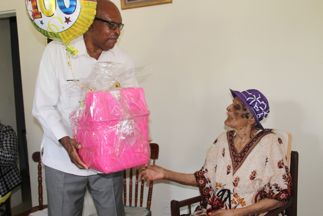 Governor General of St. Kitts and Nevis His Excellency Sir Tapley Seaton presents a gift basket to centenarian Eileen Swanston Smithen at her home in Zion Village, Gingerland on July 13, 2017, in celebration of her 100th birthday some weeks ago