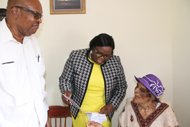 (L-r) Governor General of St. Kitts and Nevis His Excellency Sir Tapley Seaton and Hon. Hazel Brandy Williams, Junior Minister in the Ministry of Social Development in the Nevis Island Administration share a light moment with Centenarian Eileen Swanston Smithen, moments after he presents her with the royal birthday card from Her Majesty Queen Elizabeth II at her home in Zion Village on July 13, 2017