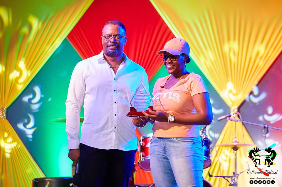 """Hon. Mark Brantley, Deputy Premier of Nevis and Minister of Culture presents token of appreciation to Chevaughn Claxton on behalf of her father Oldain """"Sandy"""" Claxton on July 04, 2017, for his long standing contributions at the Cultural Village"""