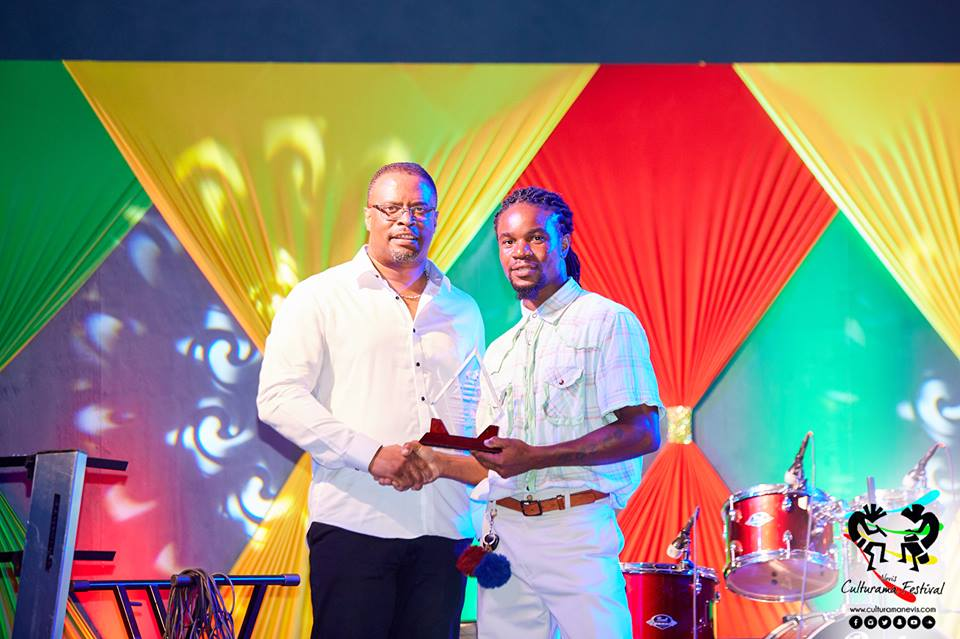 """Hon. Mark Brantley, Deputy Premier of Nevis and Minister of Culture presents token of appreciation to Glenville """"DJ Denny"""" Fahie on behalf of Samuel """"Fish"""" Richards on July 04, 2017, for his long standing contributions at the Cultural Village"""