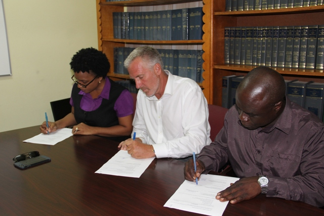 (L-r) Permanent Secretary in the Ministry of Health Nicole Slack-Liburd, Representative for ENCLAVE Resources Geoffrey Folsom and Manager of the Nevis Solid Waste Management Authority Andrew Hendrickson sign agreement for disposal of waste metal and cardboard on Nevis at a ceremony at the Legal Department's conference room on July 17, 2017