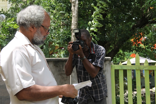 Dr. Whitman Browne, Nevisian author of three publications on the M.V, Christena Disaster in St. Kitts and Nevis in 1970, takes a picture of Lester Blackett while collecting photographs at the Memorial Service at the Alexander Hamilton Museum Grounds on August 01, 2017, commemorating the 47th anniversary of the disaster