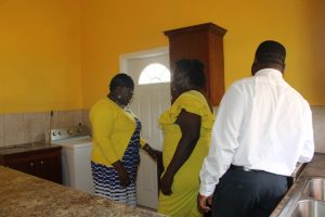 Ms. Stephanie Freeman (middle) showing Hon. Hazel-Brandy Williams, Junior Minister of Social Development in the Nevis Island Administration and Mr. Keith Glasgow, Permanent Secretary in the Ministry the kitchen area of her new home presented to her on October 19, 2017, under the Ministry of Social Development's Community Home Assistance Programme.