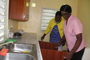 Homeowner Mrs. Yvonne Stanley (right) and Hon. Hazel Brandy-Williams, Junior Minister in the Ministry of Social Development take a look at refurbishment work done under the Ministry's Community Housing Assistance Programme, moments after Mrs. Brandy-Williams handed over the keys on October 19, 2017