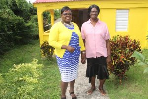 Hon. Hazel Brandy-Williams, Junior Minister in the Ministry of Social Development with homeowner Mrs. Yvonne Stanley in front her newly renovated Fig Tree home on October 19, 2017.