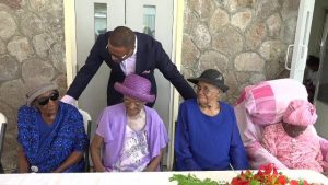 Hon. Mark Brantley, Deputy Premier of Nevis and Senior Minister in the Ministry of Social Development, sharing a light moment with four of the eight centenarians on Nevis at a ceremony at the Flamboyant Nursing Home to honour them. It was hosted by the Social Services Department, Seniors Division in the Ministry of Social Development