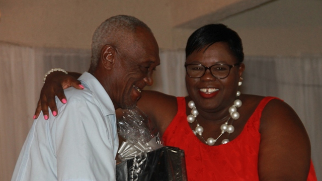 "Hon. Hazel Brandy-Williams, Junior Minister in the Ministry of Social Development presents a gift basket to Mr. Clefrin ""Shine"" Daniel, one of five men honoured for their contribution to cultural preservation on Nevis"