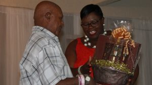 Hon. Hazel Brandy-Williams, Junior Minister in the Ministry of Social Development presents a gift basket to Mr. Norton Cornelius, one of five men honoured for their contribution to cultural preservation on Nevis