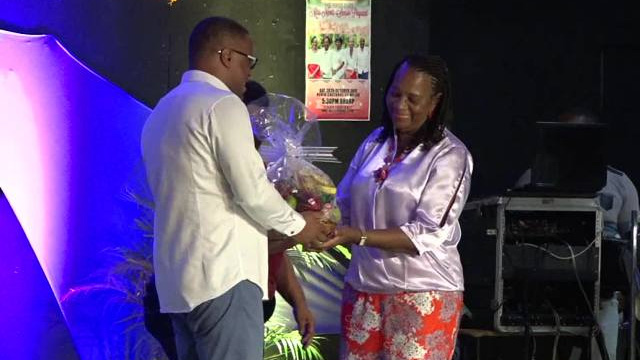 Deputy Premier of Nevis Hon. Mark Brantley presenting a fruit basket to Mrs. Garcia Hendrickson, outgoing Coordinator of the Department of Social Services Senior's Division in the Ministry of Social Development, at the Miss Nevis Senior Pageant at the Nevis Cultural Complex on October 28, 2017
