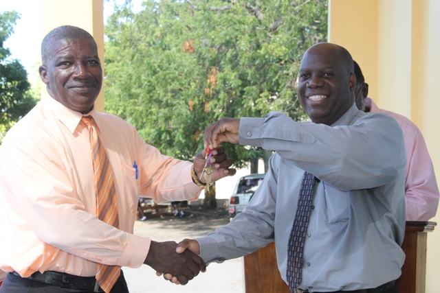 Mr. Edson Elliott, Education Officer in the Department of Education who is responsible for secondary schools at a handing over keys to the new addition to the Charlestown Secondary School to Principal, Mr. Juan Williams at a handing over ceremony at the school compound on December 13, 2017
