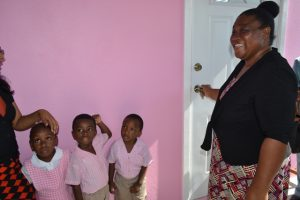 Elated Gingerland Preschool Supervisor Mrs. Pamella Elliott-Lawrence, opens the door to the newly renovated and expanded Gingerland Preschool with some students and staff looking on, moments after receiving the keys from education officials on December 12, 2017