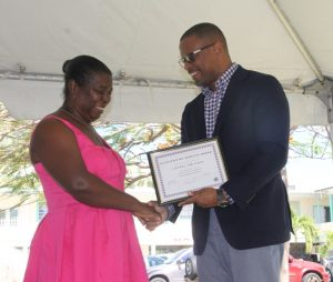 Minister of Health Hon. Mark Brantley presents a plaque to Nurse Manager Laurel Smithen on behalf of the Alexandra Hospital at their Pre-Christmas Programme on December 13, 2017, for her dedication to Nursing