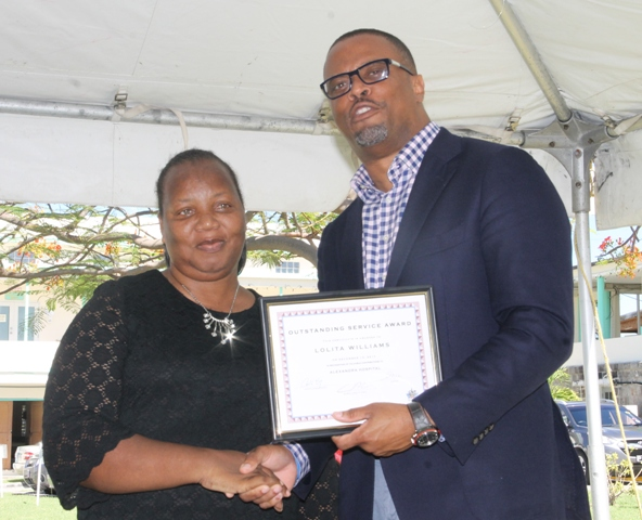 Minister of Health Hon. Mark Brantley, presents a certificate of recognition to Mrs. Ermine Jeffers, Coordinator of the Community Nursing Services on behalf of the Public Health Unit, at the hospital's Pre-Christmas Programme on December 13, 2017, for their outstanding performance in 2017