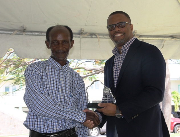 "Minister of Health Hon. Mark Brantley presents a plaque to retired Orderly Mr. Anthon ""the dancing orderly"" Hicks on behalf of the Alexandra Hospital, at the hospital's Pre-Christmas Programme on December 13, 2017, for his dedication to duty"