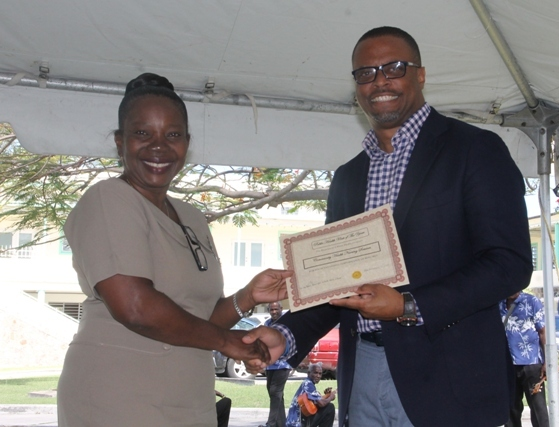 Minister of Health Hon. Mark Brantley presents a plaque to Ms. Lolita Williams on behalf of the Alexandra Hospital at the hospital's Pre-Christmas Programme on December 13, 2017, for her contribution to the Housekeeping Department