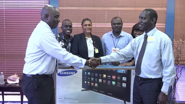 (Right) Mr. Oscar Walters, General Manager for S.L. Horfords (Nevis Center) presents two Samsung 43 inch television sets to Mr. John Hanley, Acting Permanent Secretary in the Ministry of Tourism recently for use at the Vance W. Amory International Airport. Looking on are (l-r) Dawson Ottley, Tourism Officer in the Ministry of Tourism, Ms. Shelagh James, Communications Officer in the Ministry of Tourism, Mr. Daron Sutton, Manager of the Vance W. Amory International Airport and Mrs. Collette Weeks, Protocol Officer at the airport