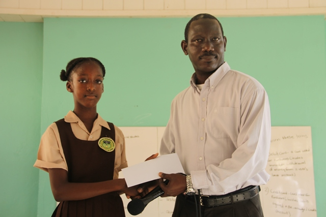 Ms. Alexzandra Weekes former student of the Joycelyn Liburd Primary School, receives her winning cheque at the local level in the Junior Category of the 2017 Florida Caribbean Cruise Association Foundation Essay Competition from Mr. John Hanley, Acting Permanent Secretary in the Ministry of Tourism on behalf of Hon. Mark Brantley, Premier of Nevis and Minister of Tourism at morning devotions at the Gingerland Secondary School on January 22, 2018