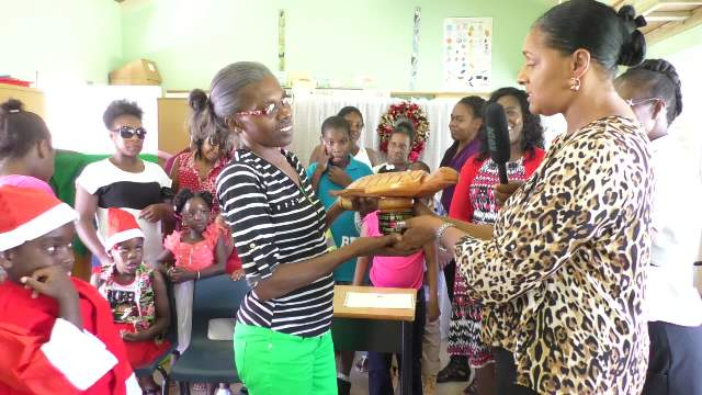 Ms. Shelagh James, Communications Officer in the Ministry of Tourism (right) presenting Mrs. Jennifer Liburd a teacher at the Cecele Browne Integrated School with a trophy on behalf of the school for winning the Ministry of Tourism's 2018 Calendar Competition