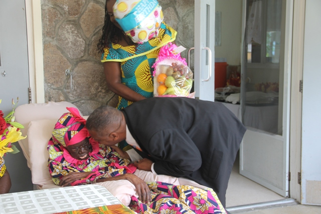 "Hon. Eric Evelyn, Minister responsible for Social Development, presents birthday celebrant Ms. Celian ""Martin Powell with a fruit basket at her 106th birthday celebration at the Flamboyant Nursing Home on January 19, 2018"
