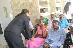"Senator Wendy Phipps, Minister of State in the Ministry of Health in the Federal Government interacting with seniors including three centenarians (second row) at the Flamboyant Nursing Home on Nevis during the 106th birthday celebration of Ms. Celian ""Martin"" Powell, the Federation's eldest living centenarian on January 19, 2018"