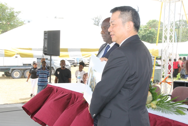 Republic of China (Taiwan) Resident Ambassador to St. Kitts and Nevis His Excellency Chiou Gow-Wei (left) presents Minister of Agriculture Hon. Alexis Jeffers with a cheque of US$1400,000 at the Department's 24th Annual Open Day opening ceremony at the Villa Grounds on March 22, 2018, to purchase a backhoe for land clearing on Nevis