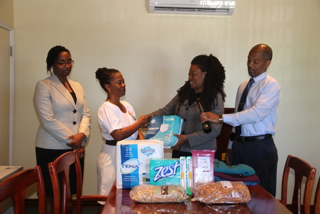 (Middle l-r) Ms. Donna Hanley, Nurse Manager of the Flamboyant Nursing Home receives a donation from Mrs. Francine Anson, Founder of the Helping Hands Initiative on February 28, 2018, while Ms. Marlene Jeffers, Assistant Hospital Administrator (extreme left) and Mr. Gary Pemberton, Hospital Administrator look on