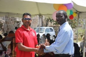 Mr. John Hanley, Acting Permanent Secretary in the Ministry of Tourism (left) presenting an award to Mr. Ganeshram Kistoo in recognition of his 15 years of service at the Nevisian Heritage Village in Gingerland at the 15th anniversary celebration on February 22, 2018