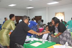 Participants greeting each other at the Department of Gender Affairs' Health is Wealth Seminar for Women and Girls at the St. Paul's Anglican Church Hall on March 08, 2018