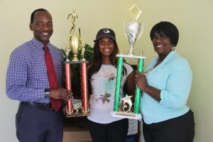 Mr. Kevin Barrett, Permanent Secretary in the Ministry of Education and Library Services (left) and Mrs. Terres Dore, Education Officer (right) presenting winning trophies to Ms. Latoya Jeffers, Principal of the Charlestown Primary School, winners of the 2018 Gulf Insurance Inter-primary Schools Athletics Championship on April 05, 2018, at the Ministry of Education at Marion Heights