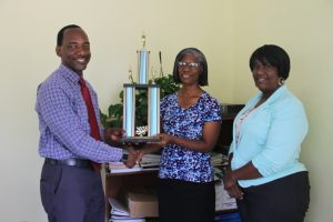 Mr. Kevin Barret, Permanent Secretary in the Ministry of Education and Library Services (left) and Mrs. Terez Dore, Education Officer (right) presenting a trophy to Mrs. Barbara Hendrickson, Principal of the Joycelyn Liburd Primary School, second place winners in the 2018 Gulf Insurance Inter-primary Schools Athletics Championship on April 05, 2018, at the Ministry of Education at Marion Heights