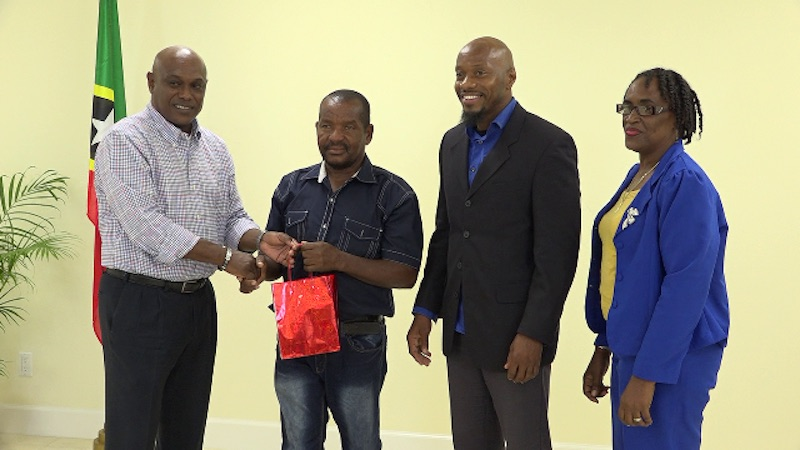 "(L-r) Mr. Vernel Powell, Assistant Director of the St. Christopher and Nevis Social Security presents a token of appreciation to Mr. William ""Bully"" Perkins a 13-year driver and messenger with the Ministry of Health, at the Board's Nevis Branch office at Pinney's Estate on May 18, 2018. Looking on are Board members Mr. Timothy Caines and Mrs. Jacqueline Brooks-Jeffers look on"